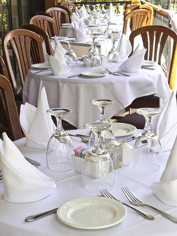 Table settings on white linen at outdoor restaurant